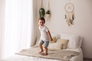 bambino 3 anni gioca sul letto