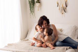 mamma e figli mesi giocano sul letto