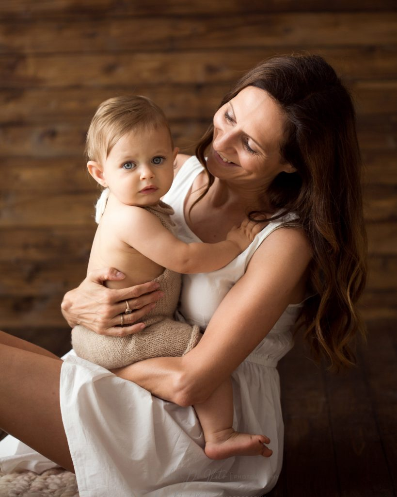 bambino 10 mesi studio fotografico ritratto fondo legno