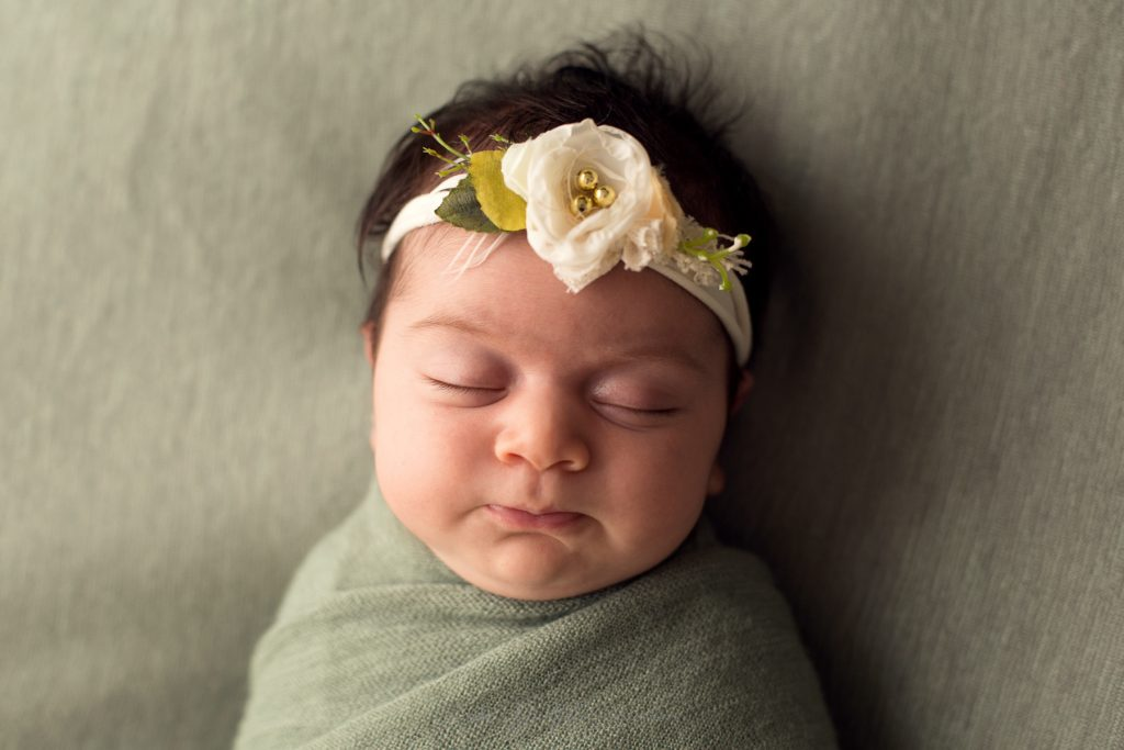 ritratto di neonata con fiore in testa