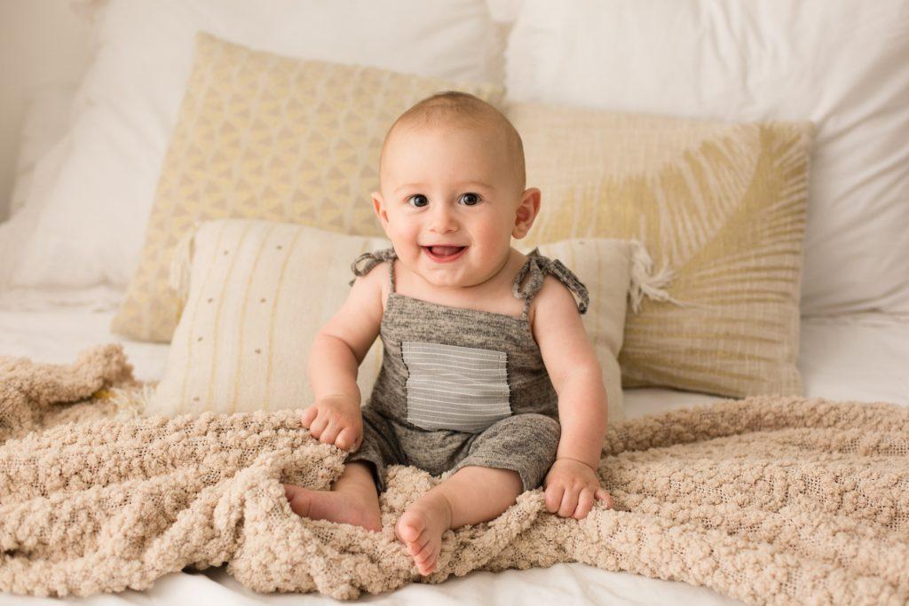 bebè sul letto ride