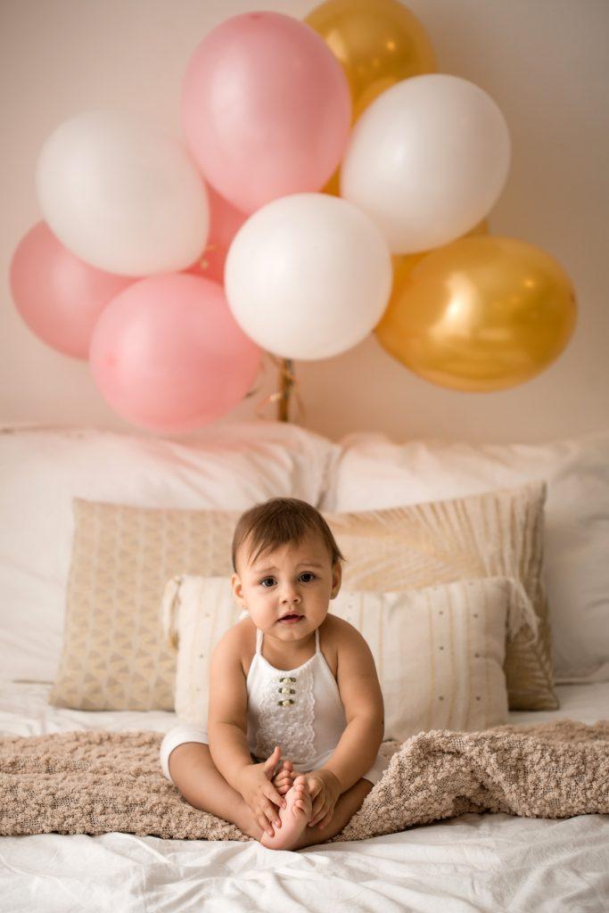 bambina di 12 mesi gioca sul letto con palloncini