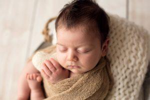 ritratto in studio fotografico di neonata con cuoricino in stoffa in mani neonata nel secchio