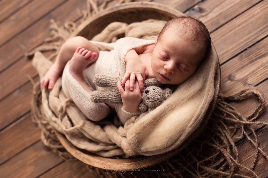 neonato in ciotola di legno e orsetto