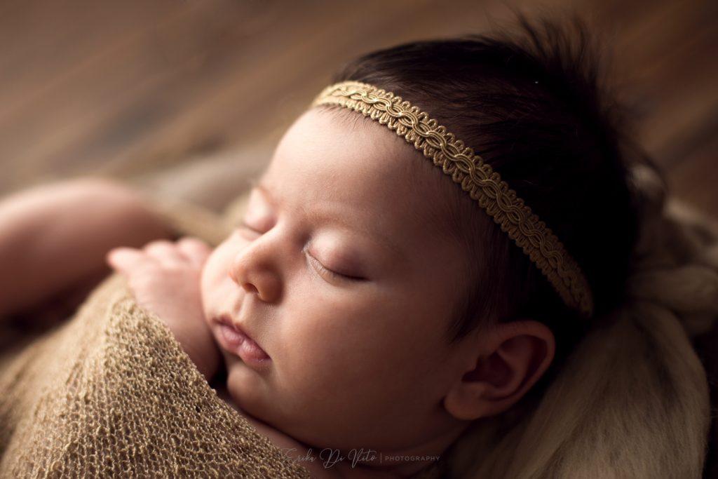 viso neonata con vascia dorata