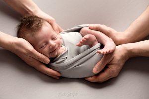 mani genitori con neonato che sorride